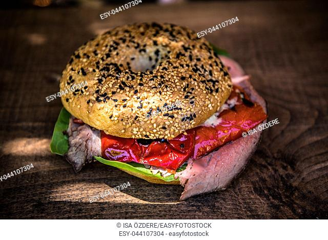 Homemade beef steak burger with meat and roasted red pepper,cherry tomatoes and vegetables on wooden cutting. Rustic style image