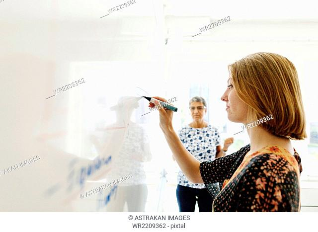 Teacher watching female student writing on whiteboard in classroom