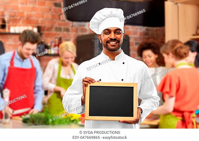 happy indian chef with chalkboard at cooking class