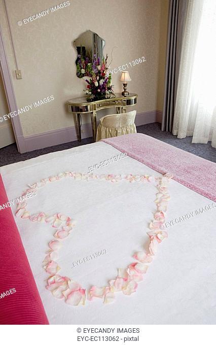 Flowers in heart shape on hotel bed