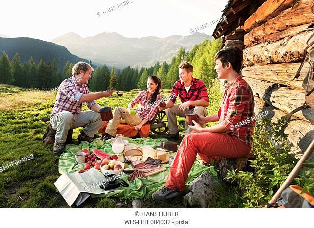 Austria, Salzburg County, Men and women having picnic near alpine hut at sunset