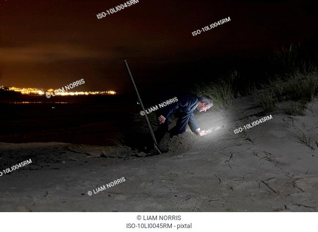 A businessman digging in the sand