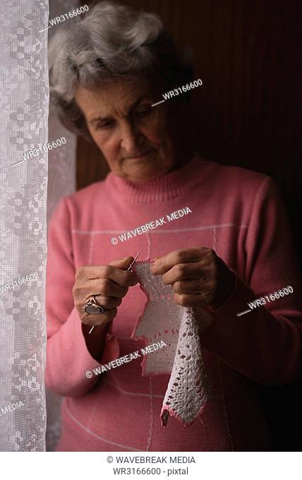 Senior woman knitting wool at home