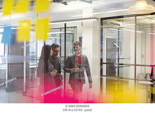 Business people walking and talking in office corridor