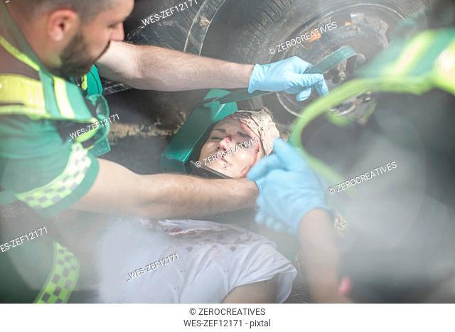 Paramedics fixing head of car crash victim on stretcher