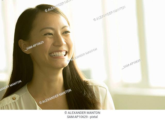 Singapore, Mid adult woman smiling with window in background