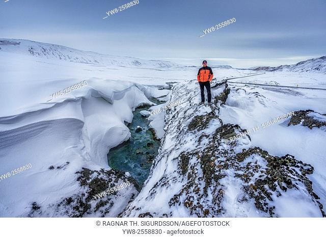 Man standing by river, Lake Myvatn, Iceland
