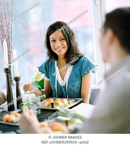A woman eating sushi at a dinner party