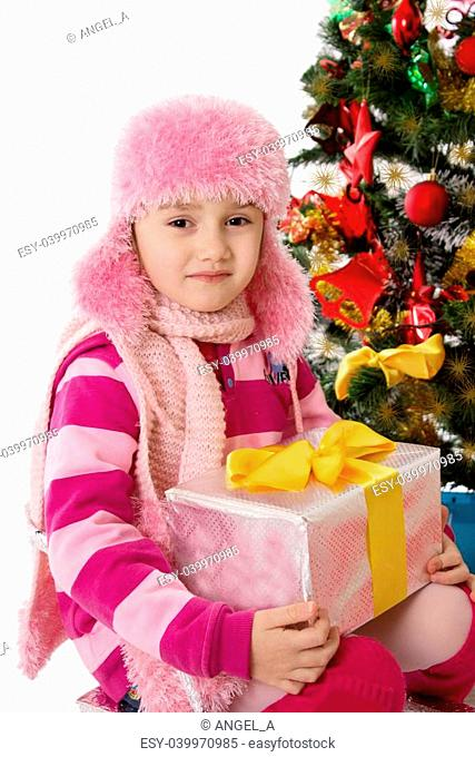 Pretty girl in pink fur hat holding present under Chritmas tree