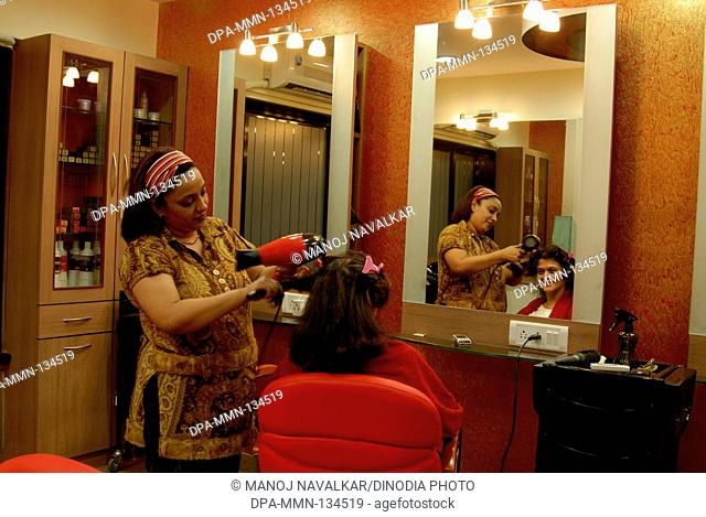 Hair styling and color highlighting  treatment in beauty parlour at Vakola ; Santacruz ; Mumbai Bombay ; Maharashtra ;  India NO MR