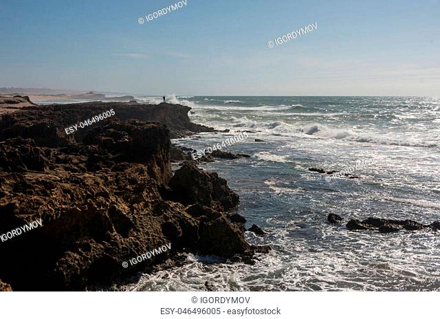 Waves breaking of cliffs near Oualidia lagoon in same name village in Atlantic ocean coast, Morocco