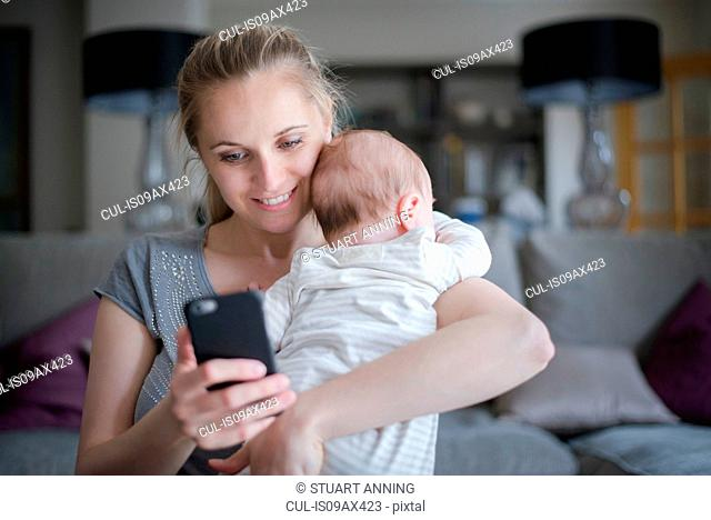 Mother holding baby boy whilst using smartphone