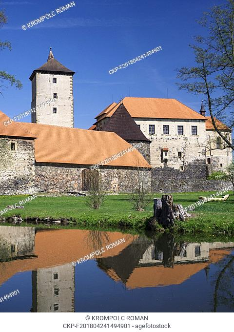Water Castle Svihov, gothic granary behind the water canal - the Uhlava river. Under the tree is a massive carved wooden bench