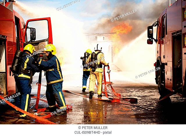 Firemen training, team of firemen extinguishing mock helicopter fire at training facility