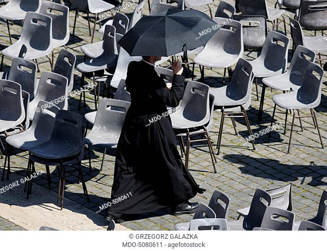 A priest protecting himself from the sun under an umbrella while walking among the empty chairs after Pope Francis' Wednesday General Audience on Saint Peter's...