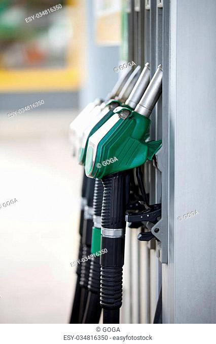 Pump nozzles at the gas station, shallow depth of field with focus on the first nozzle