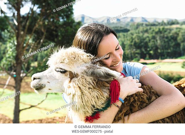 Peru, Cusco, young woman hugging an alpaca