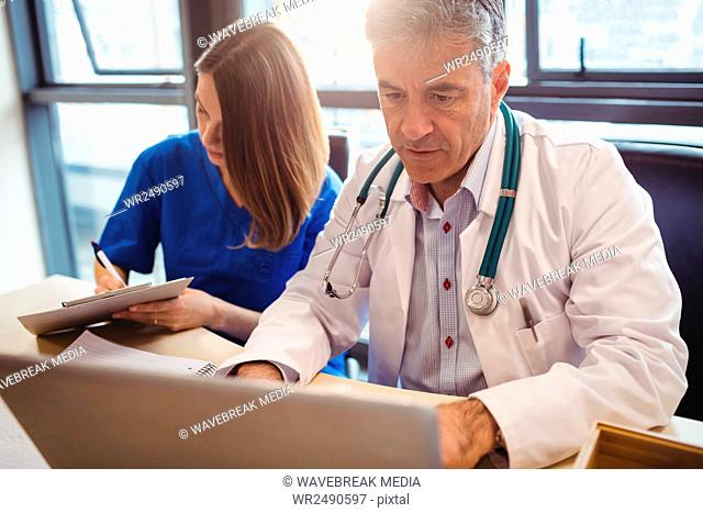 Doctor discussing with nurse over laptop