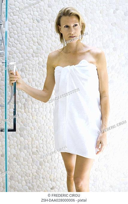 Woman in towel standing next to shower, holding onto door handle, looking away