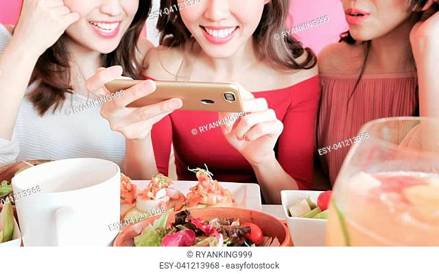 women take picture with food in the restaurant