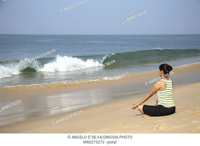 South Asian Indian young lady doing yoga sitting in padmasan posture on seashore , Shiroda , Dist Sindhudurga , Maharashtra , India MR703E