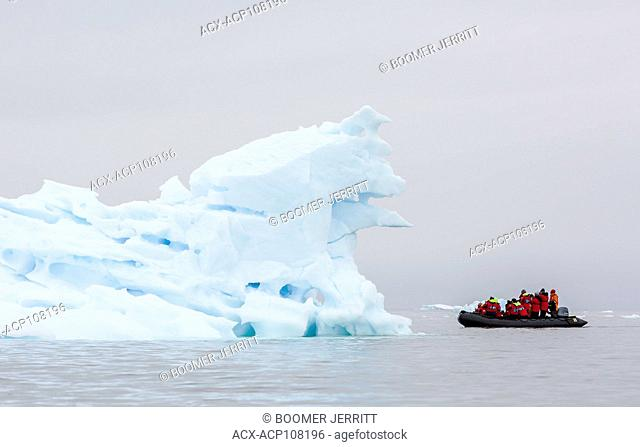 A passenger filled Zodiak cruises amongst ice flows near Pleneau Island, Antarctic Peninsula, Antarctica