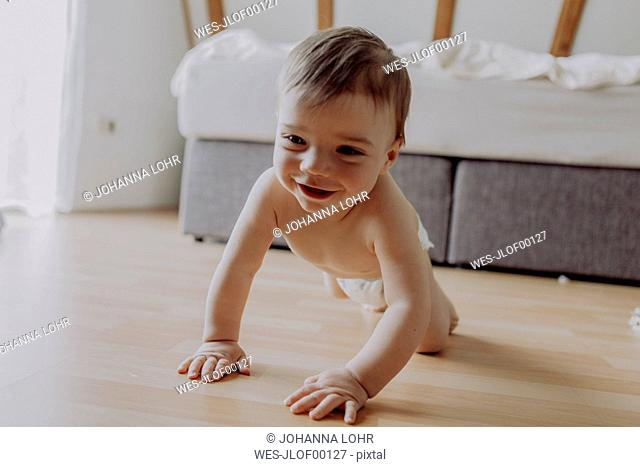 Little baby boy crawling on floor