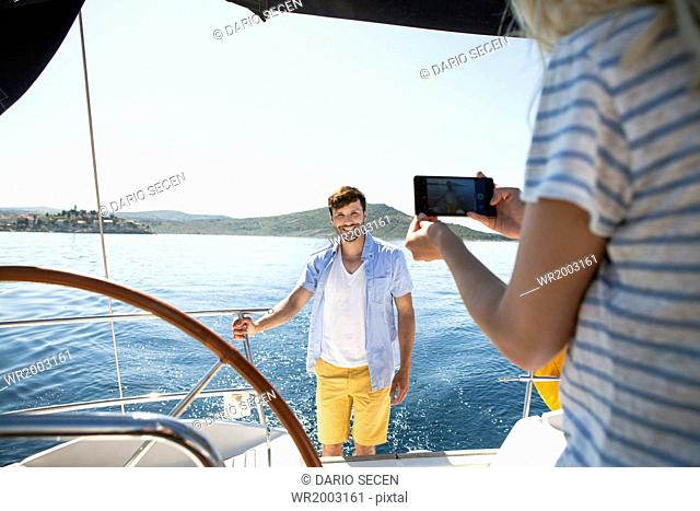 Young woman taking photo on sailboat, Adriatic Sea