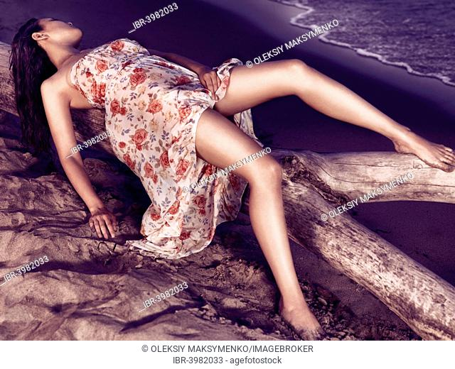 Young woman wearing a wet summer dress, lying on a piece of driftwood on a shore
