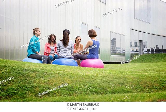 Women on fitness balls talking in exercise class on gym lawn