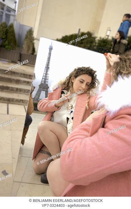 woman looking in mirror, outdoors in city, near tourist sight Eiffel Tower, at Espl. du Trocadéro, in Paris, France