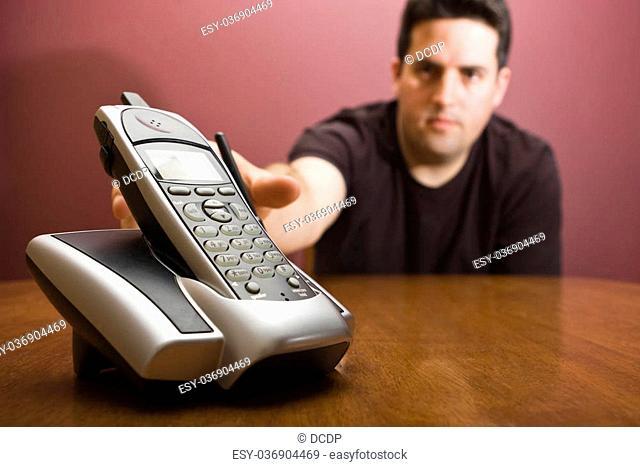 A man reaches for a cordless modern phone