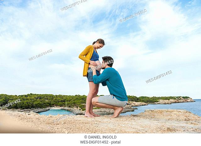 Man kissing belly of pregnant woman at the sea