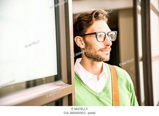 Portrait of cool businessman gazing from office doorway