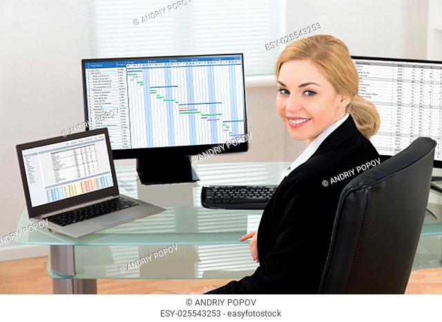 Happy Businesswoman On Office Chair Working At Computers