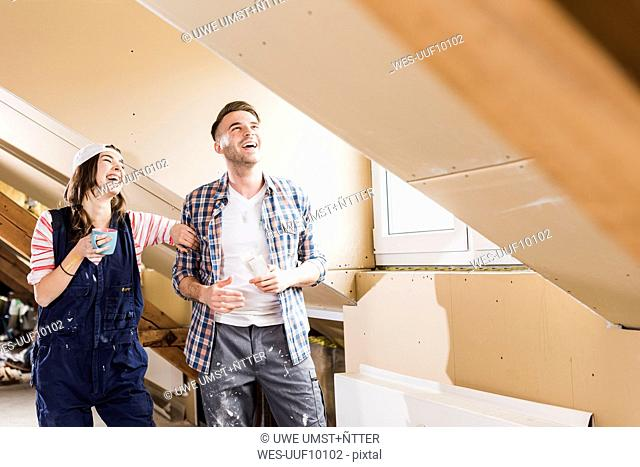 Young couple on construction site of their new home, looking at construction plan