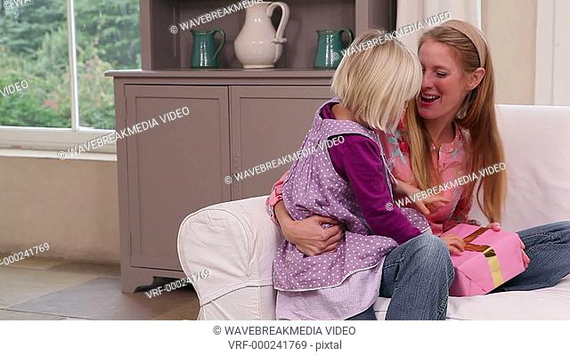 Cute little girl getting a present from her mother at home in living room
