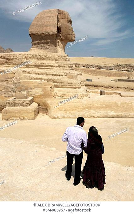 Egyptian couple on the Giza Plateau looking at the Sphinx