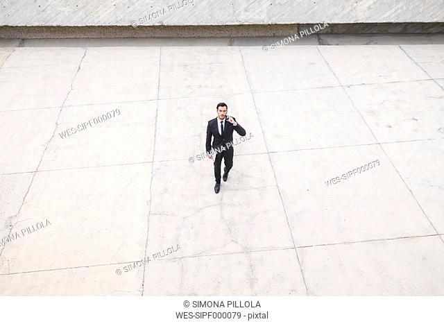 Businessman wearing black suit telephoning with smartphone