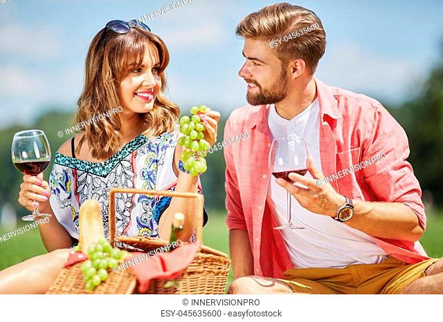 A photo of young couple picnicking at the park. They're drinking wine and eating grapes