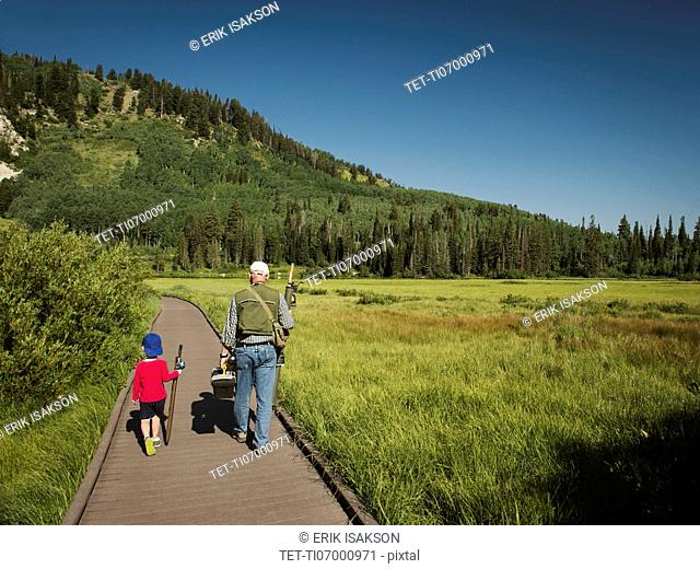 USA, Utah, Lake City, Boy (4-5) with grandfather walking on boardwalk through wetland