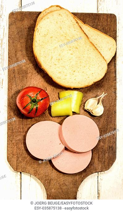 raw scalded sausage with tomato, yellow pepper, garlic and bread on a wooden board
