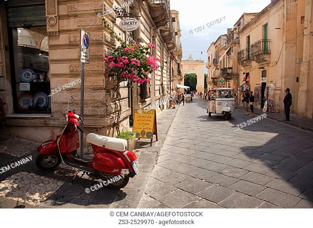 Street scene from Corso Vittoria Emanuele street the with the Porta Reale at the background, Noto, Sicily, Italy, Europe