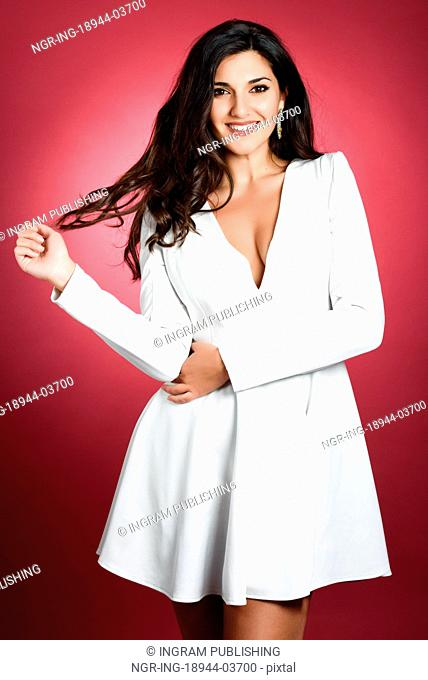 Young woman wearing short white dress on red background. Brunette girl with long hair and wavy hairstyle smiling to camera