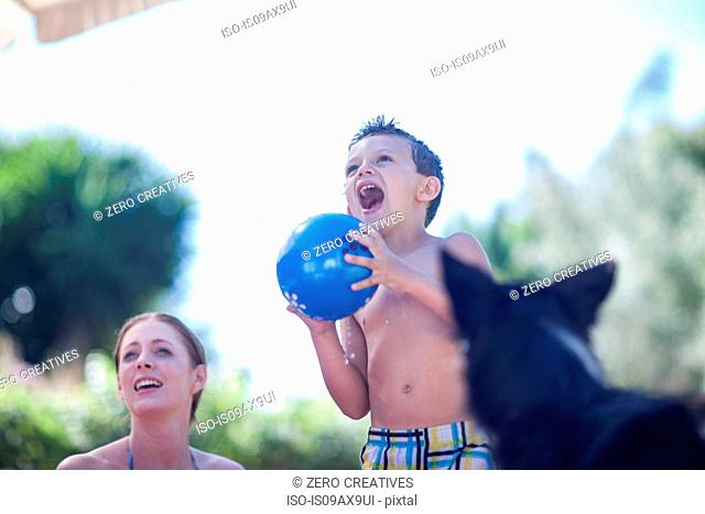 Mother and son playing ball, dog looking on