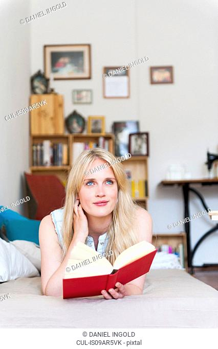 Portrait of young blond woman reading book on sofa