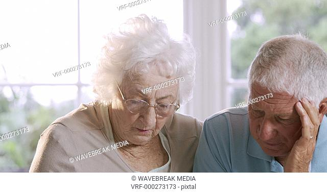 Worried senior couple talking