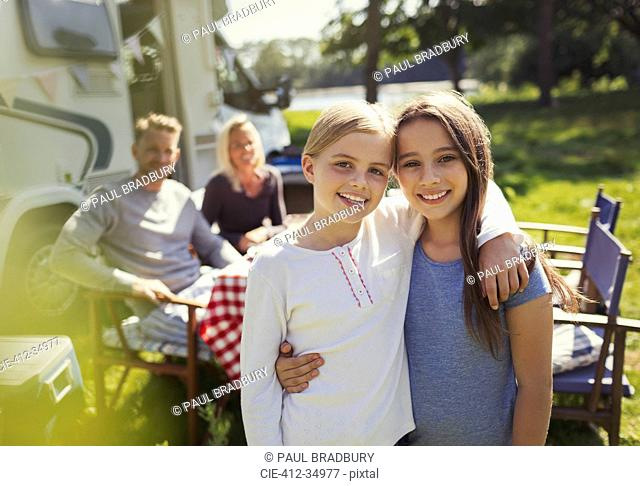 Portrait smiling sisters hugging outside sunny motor home