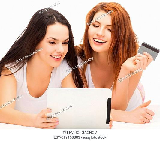 online shopping and technology concept - two smiling teenage girls with tablet pc computer and credit card