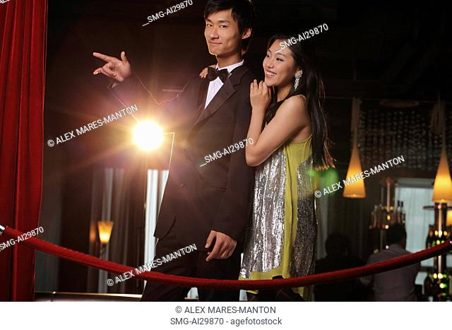 Young couple standing behind red rope at night